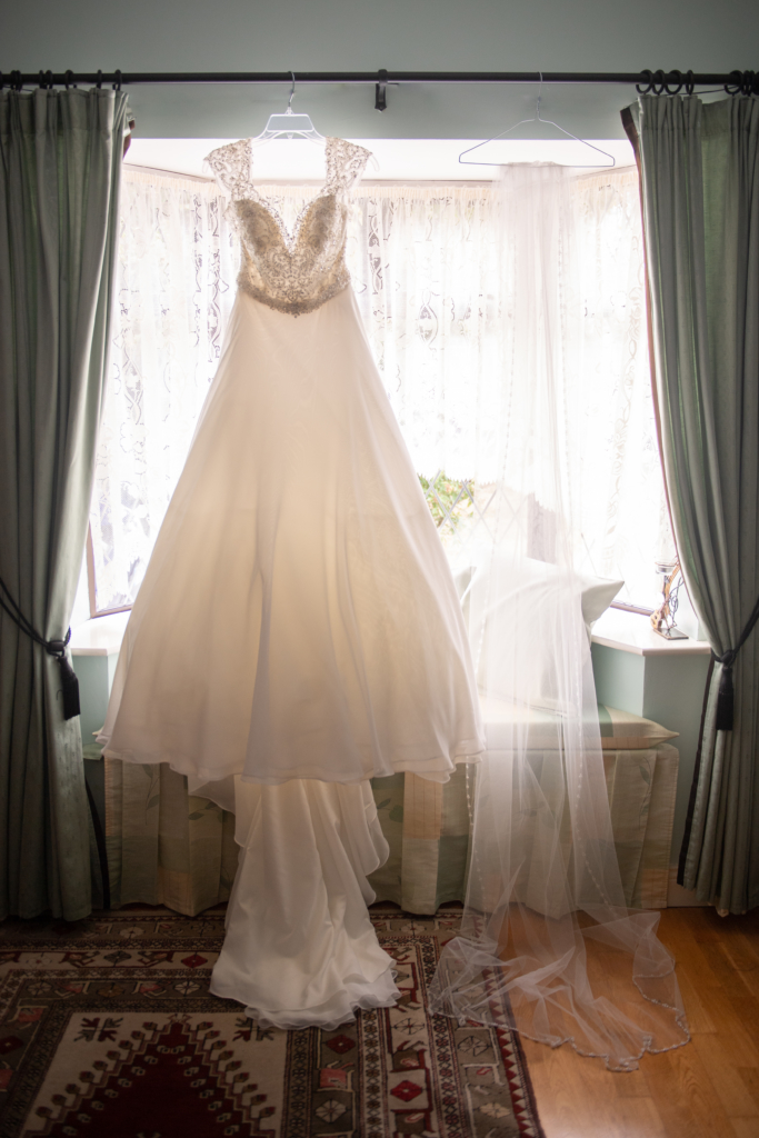 radisson blu wedding wedding dress hanging up in window by wedding photographers the fennells