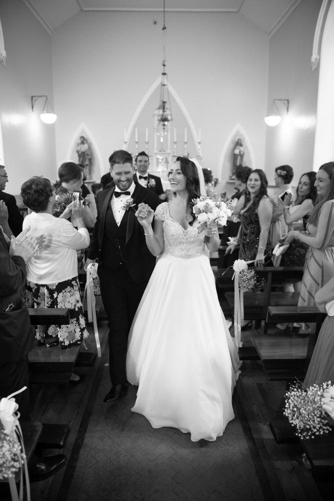 walking down aisle black and white photo by wedding photographers the fennells radisson blu wedding