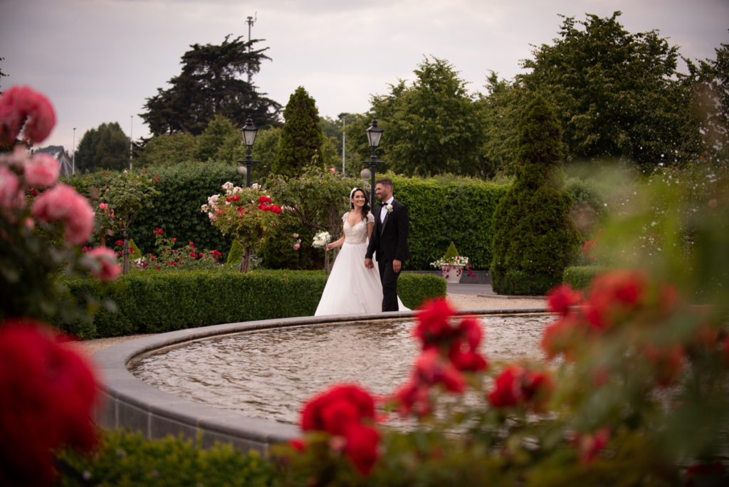 bride and groom walking through rose garden