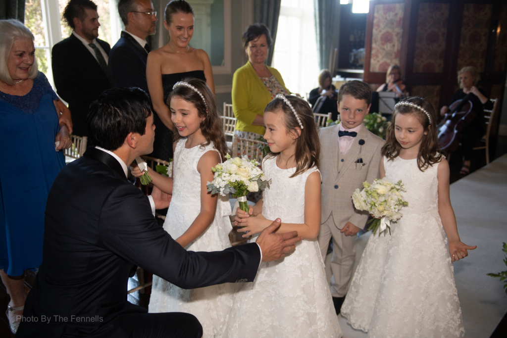 The flower girls and pageboy walking up the aisle being greeted by the groom