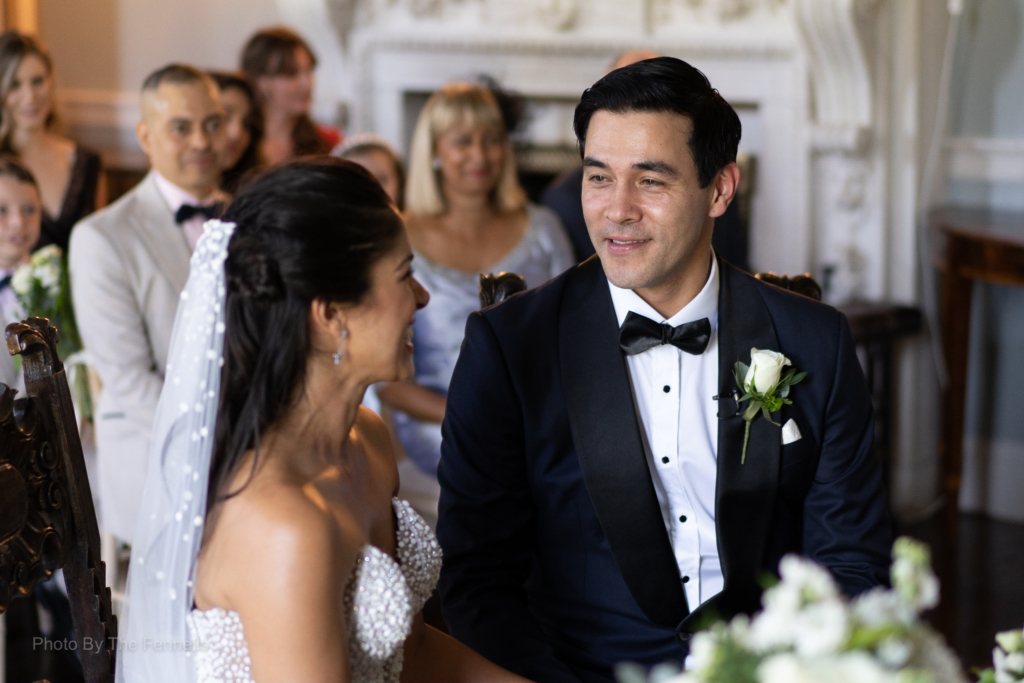 James Stewart and Sarah Roberts looking and smiling at each other while sitting at their wedding ceremony