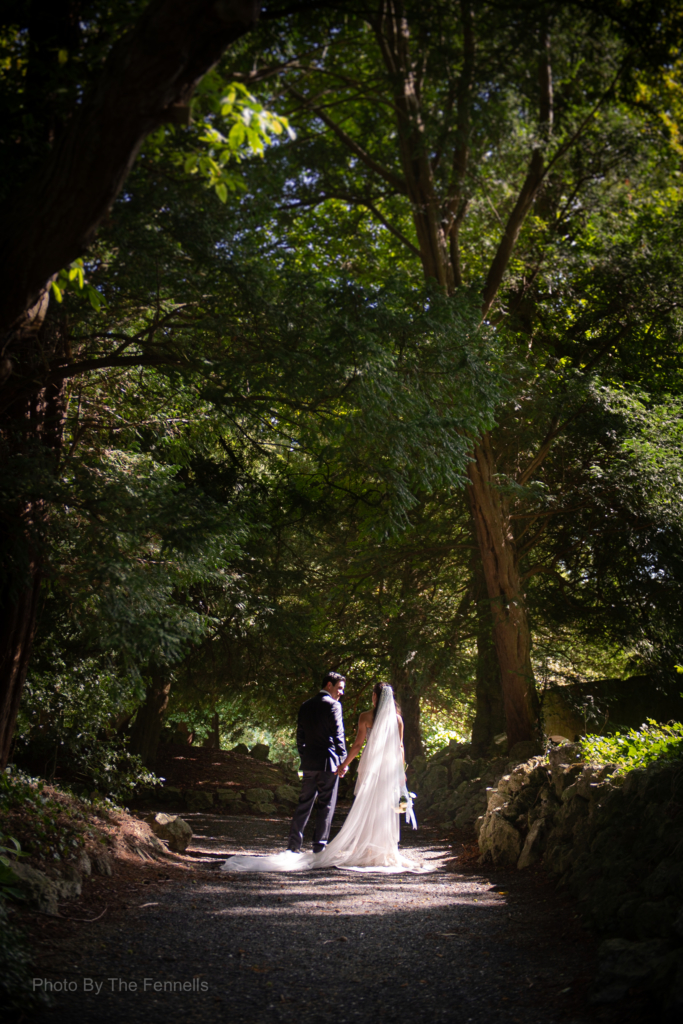 Sarah Roberts and James Stewart walking holding hands on the grounds of Luttrellstown Castle