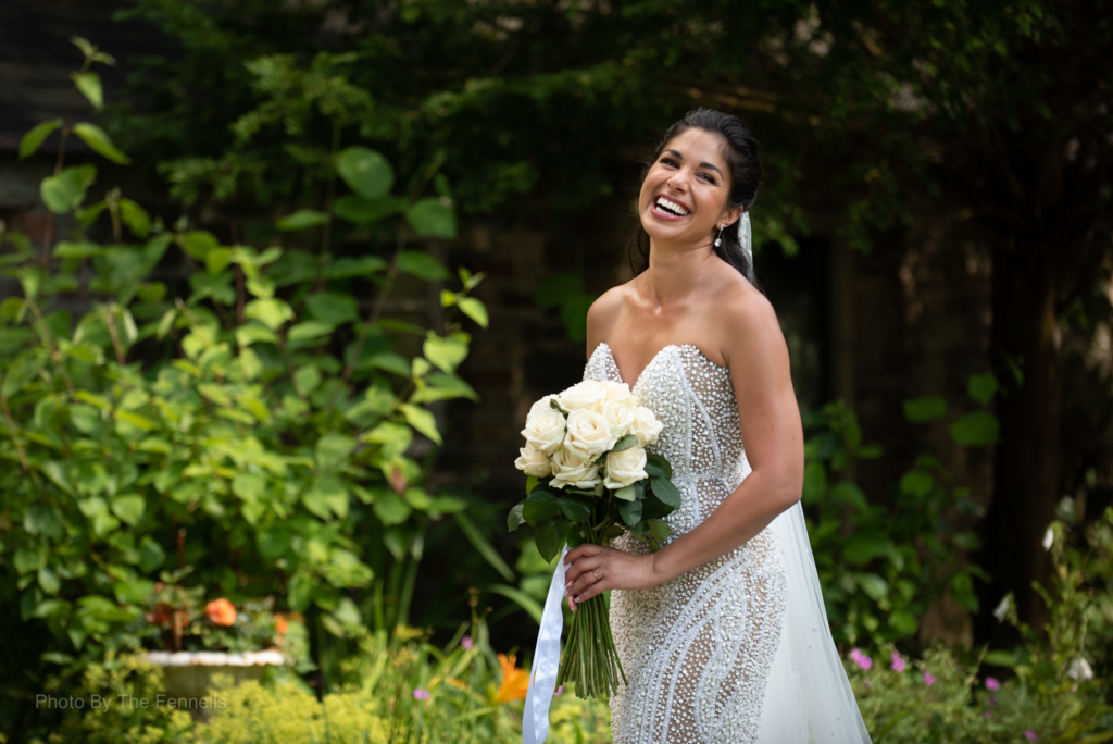 Sarah Roberts holding her wedding bouquet and laughing in the gardens at Luttrellstown Castle