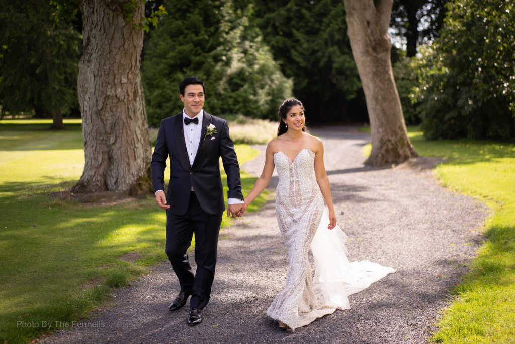 James Stewart and Sarah Roberts walking and surrounded by trees holding hands on the grounds of Luttrellstown Castle