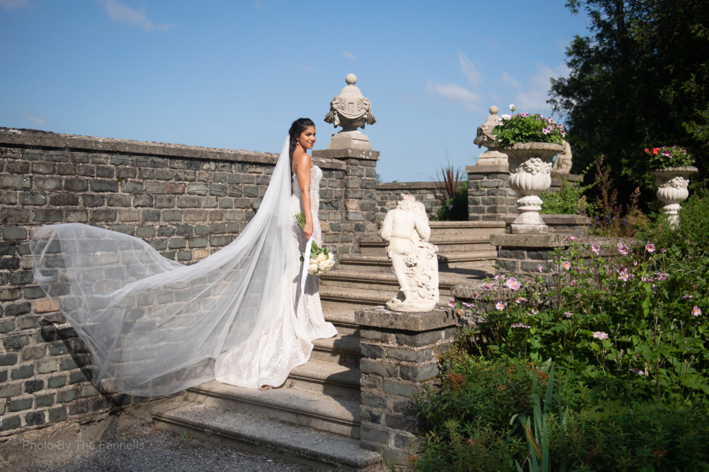 Sarah Roberts standing on the steps of Luttrellstown Castle with her veil flowing