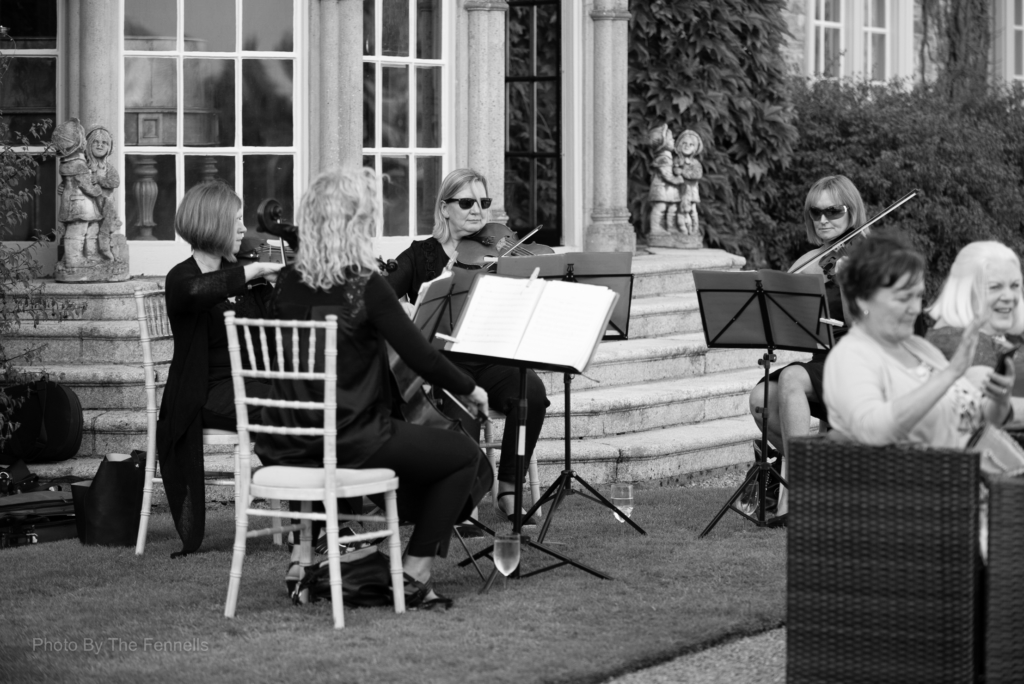 The string quartet playing outside at the home and away wedding