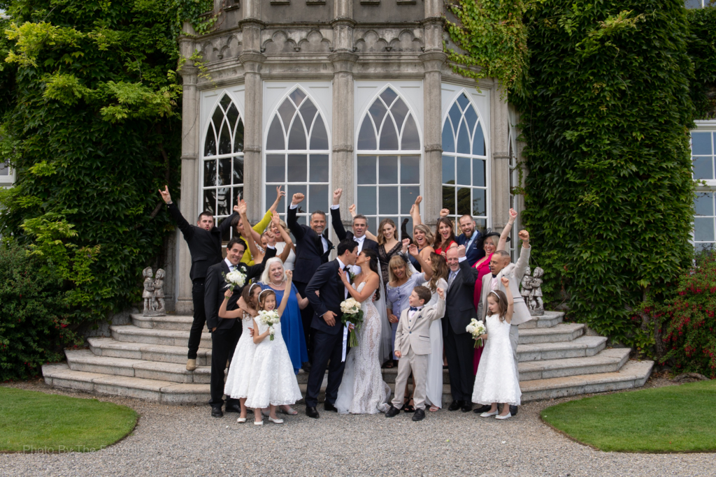 Sarah Roberts and James Stewart with their wedding guests outside on the steps of Luttrellstown Castle
