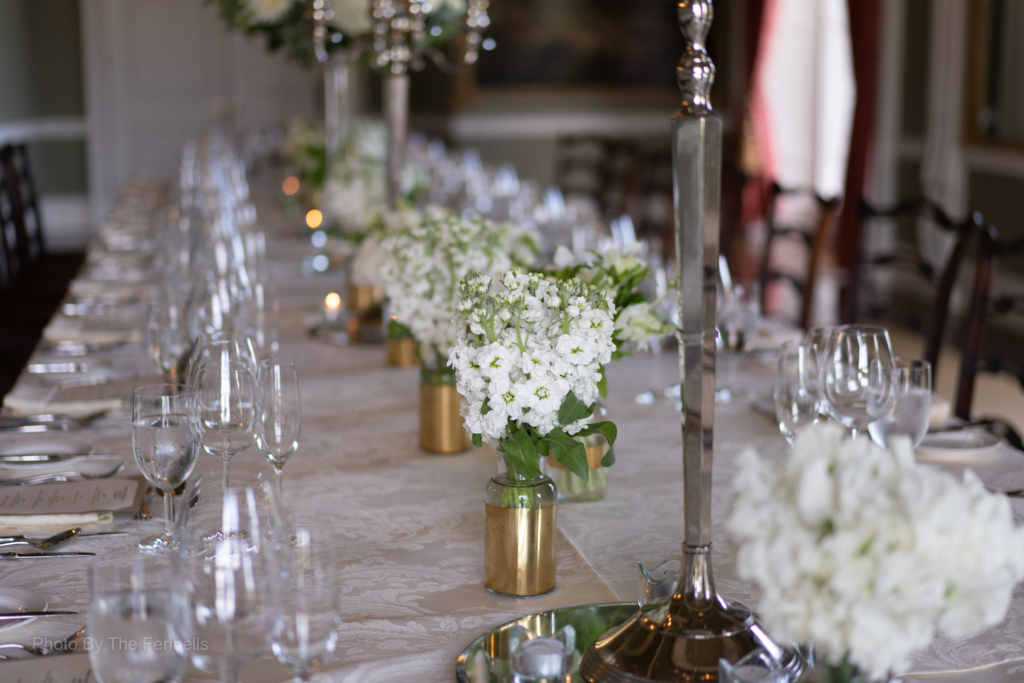 The white flowers on the table setting for the home and away wedding