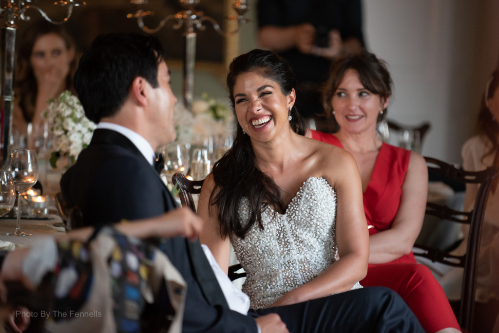 Sarah Roberts and James Stewart laughing together listening to the wedding speeches