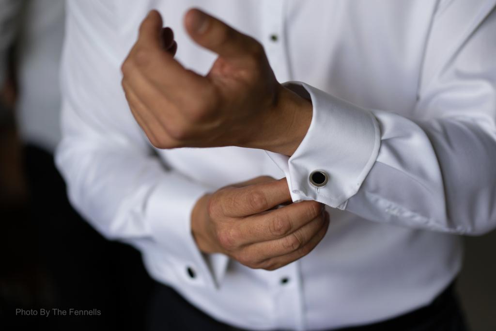 James Stewart putting on wedding cuff links