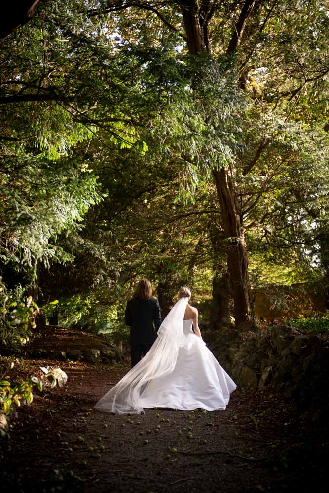 bride and groom walking holding hands through castle forrest