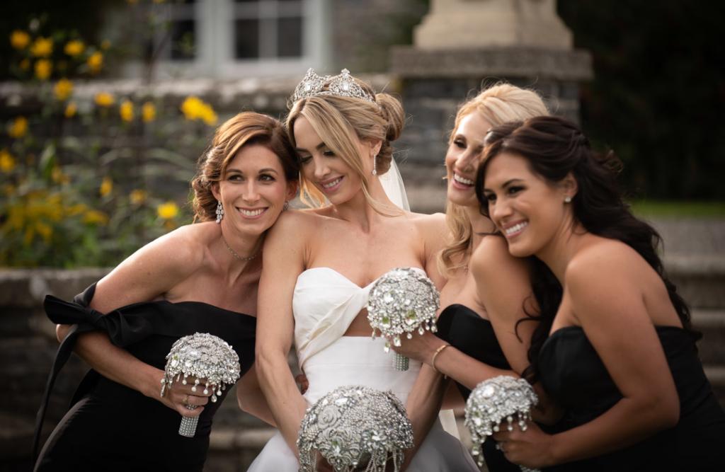 bride and bridesmaids holding diamanté bouquets laughing together