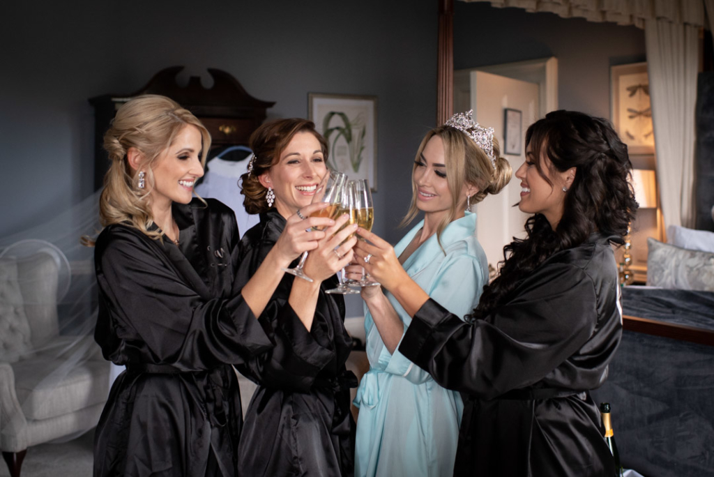 Bride and bridesmaids in robes clinking champagne glasses