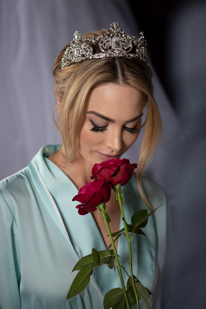 bride wearing crown smelling red rose