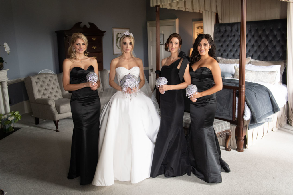 Bride in white and her bridesmaids in black dresses holding diamanté bouquets
