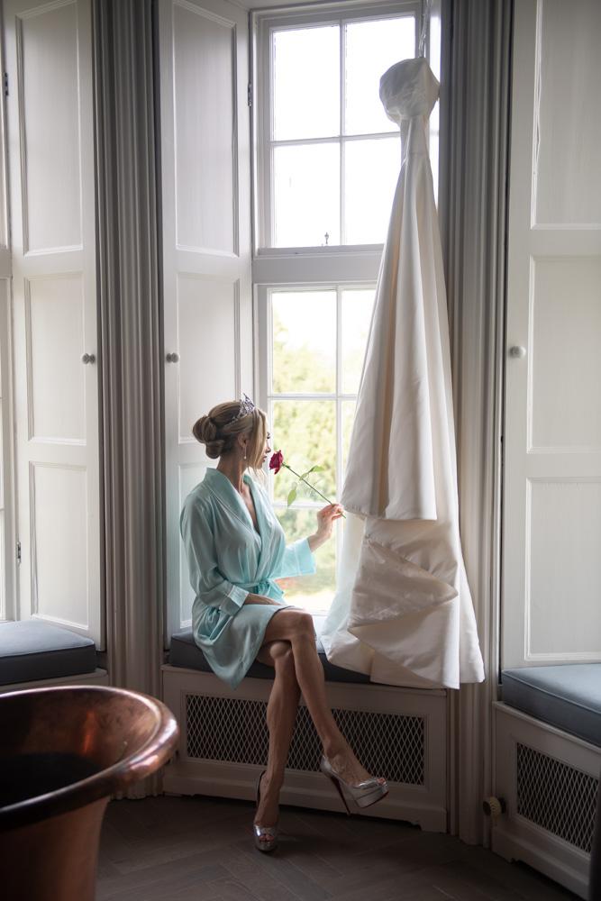 bride sitting in window beside hanging wedding dress
