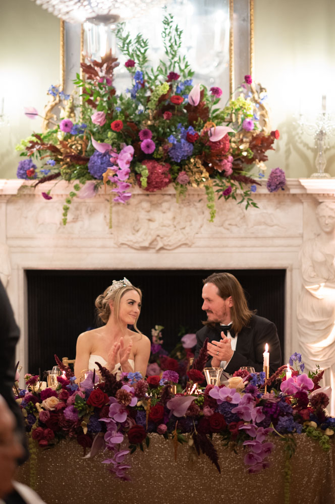 Bride and Groom at top table clapping and looking at each other during speeches