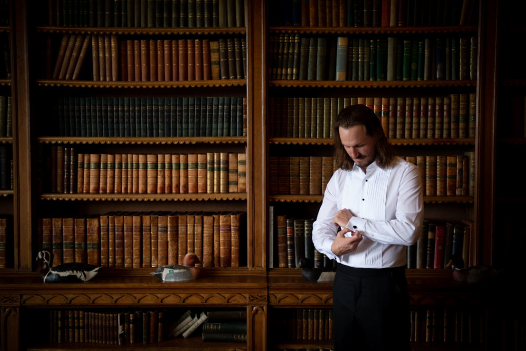 groom in white shirt fixing cufflinks in luttrellstown castle library