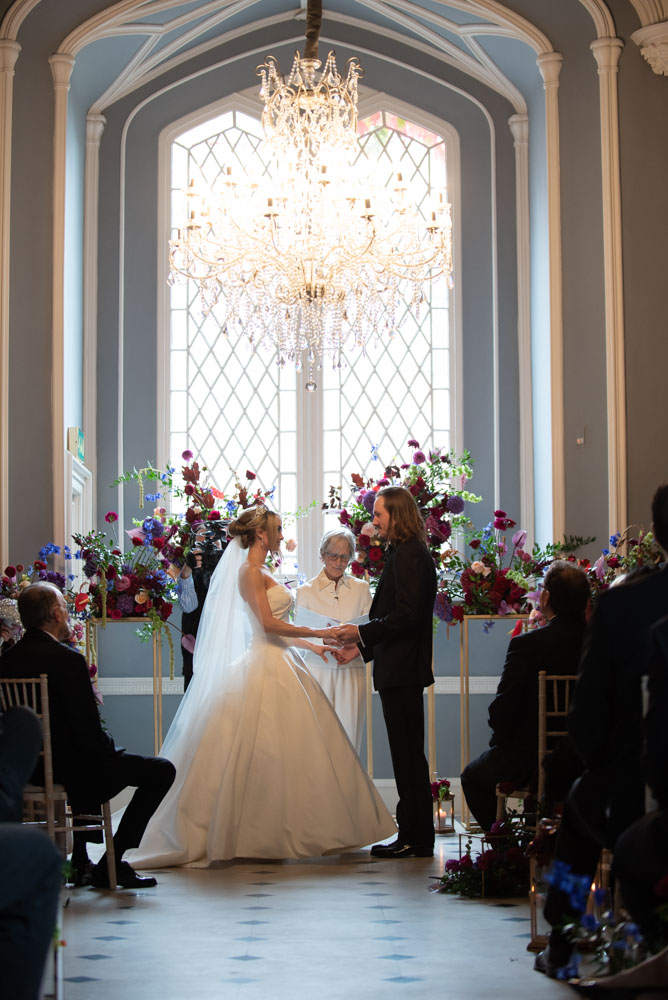 bride and groom saying vows standing under chandelier in luttrellstown castle