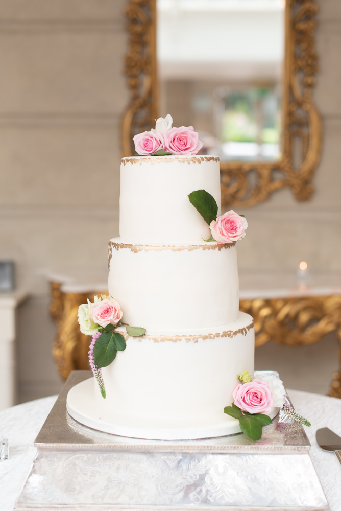 White wedding cake with gold trim and pink roses at Tankardsown House