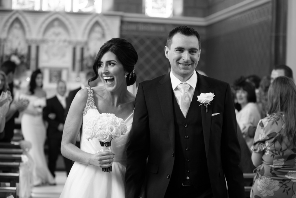 Bride and Groom laughing walking down aisle