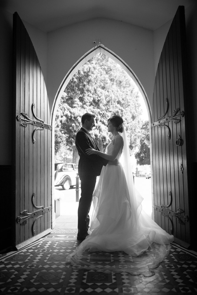 Black and white photo of Bride and Groom in the door at Church