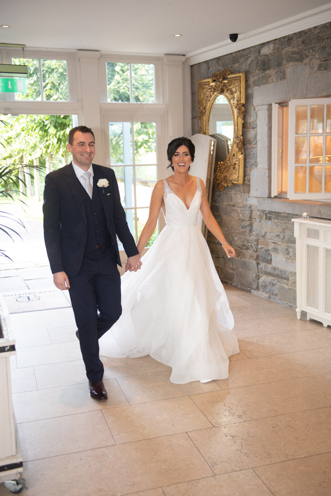 Bride and groom smiling entering the room for their dinner at Tankardstown house