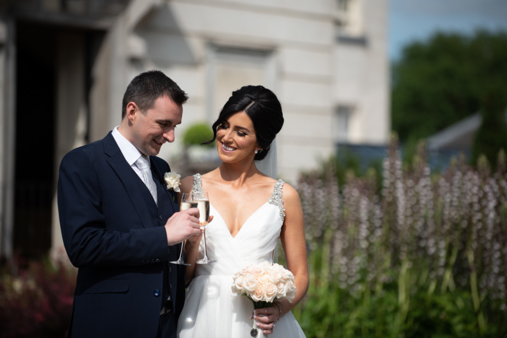 Bride and Groom clinking champagne glasses at front of Tankardstown House