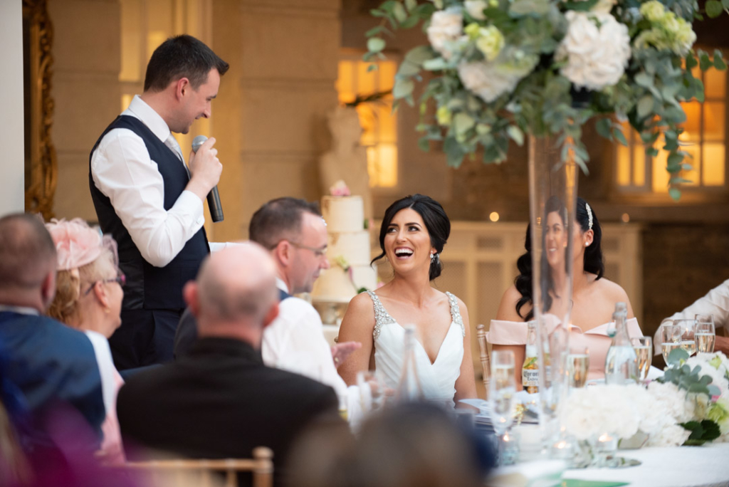Bride laughing and looking up at groom while he gives his speech
