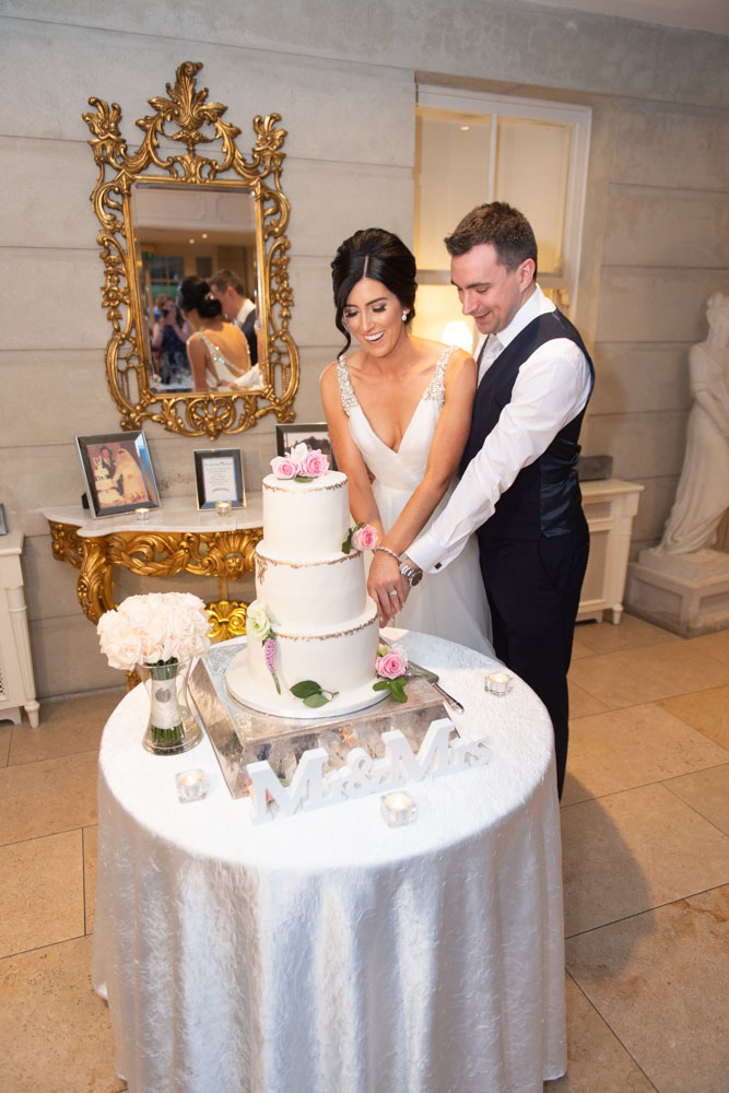 Bride and Groom cutting wedding cake at Tankardstown House