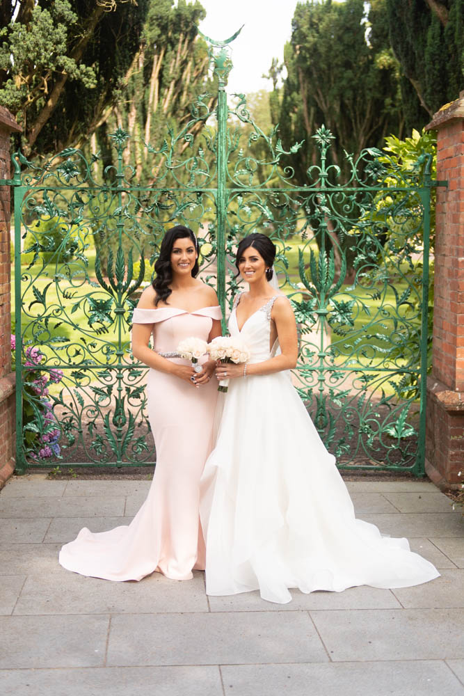 Bride and Bridesmaid in pink dress standing in front of gates for her Tankardstown House Wedding
