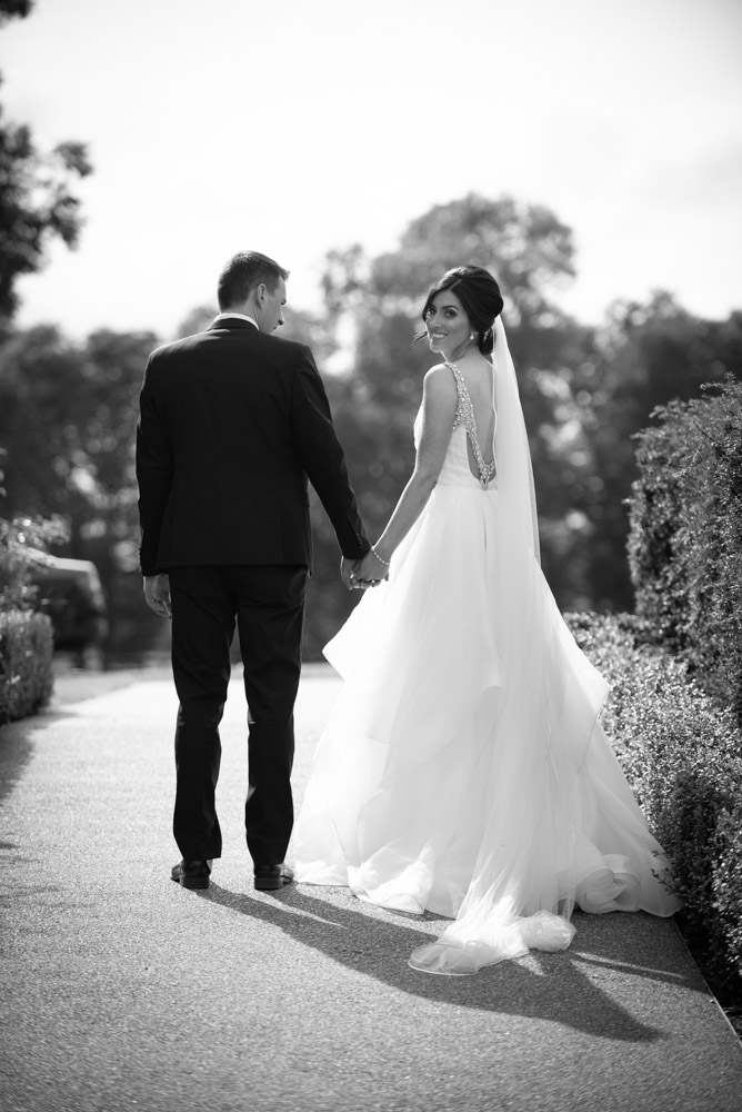 Bride and groom walking while Bride is looking back at camera at Tankardstown House