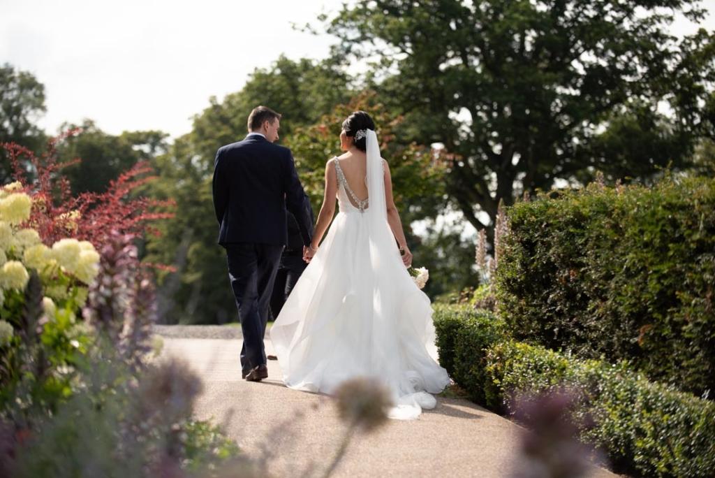 Bride and Groom walking holding hands in gardens of Tankardstown House
