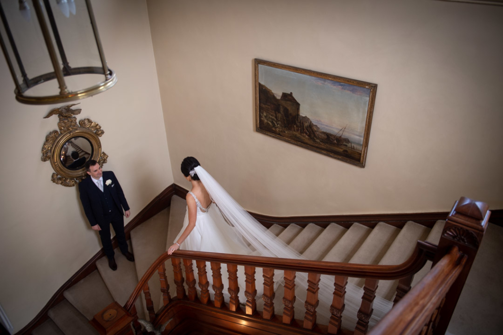 Bride walking down the stairs to groom at Tankardstown House