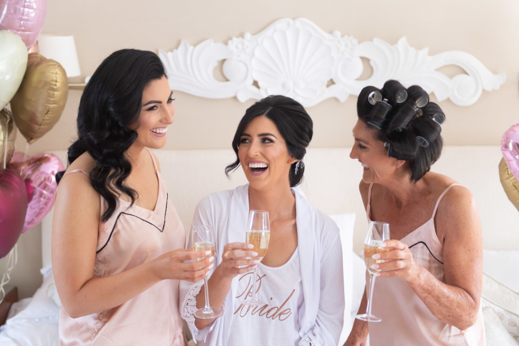 Bride and girls in pyjamas laughing with champagne on bed