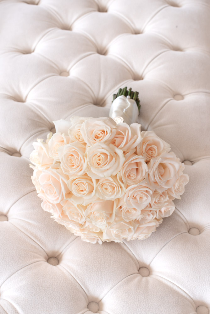 Brides flower bouquet of roses on buttoned footstool