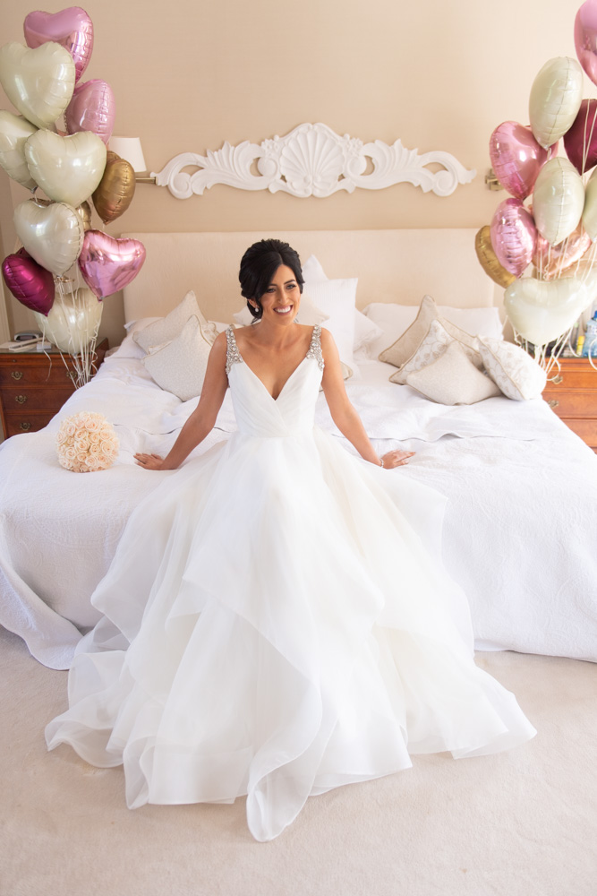 Bride sitting in wedding dress on bed with heart balloons