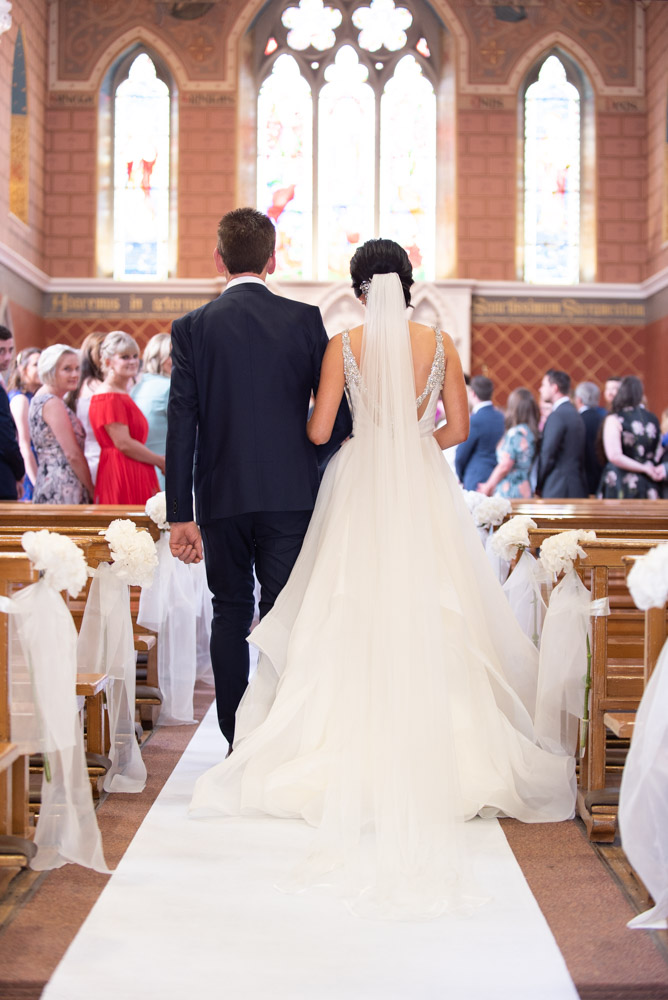 The back of Bride and her dad walking down the church aisle
