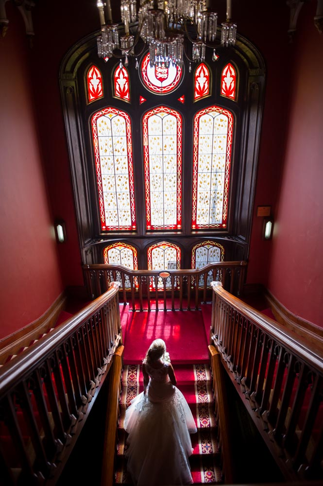 Bride walking up the stairs to the stained glass window in Dromoland Castle