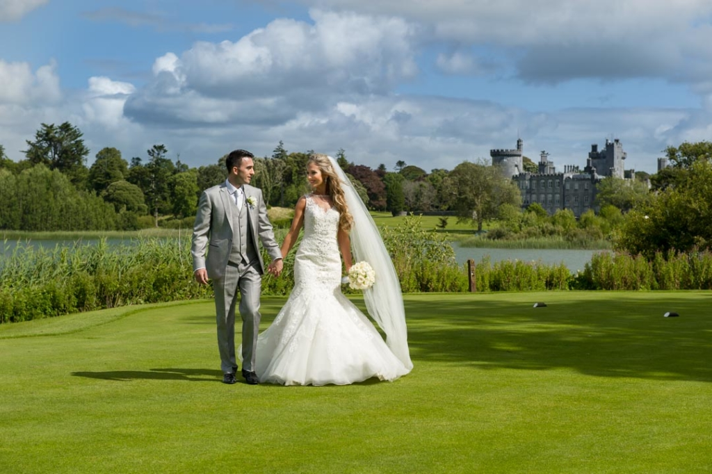 Bride and groom walking on grass with Dromoland Castle in the background