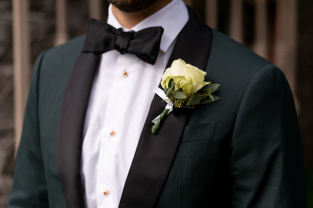 Grooms white rose buttonhole flower on his green suit