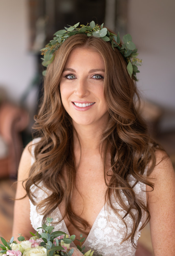 Bride with long red curly hair and a green flower crown on her head