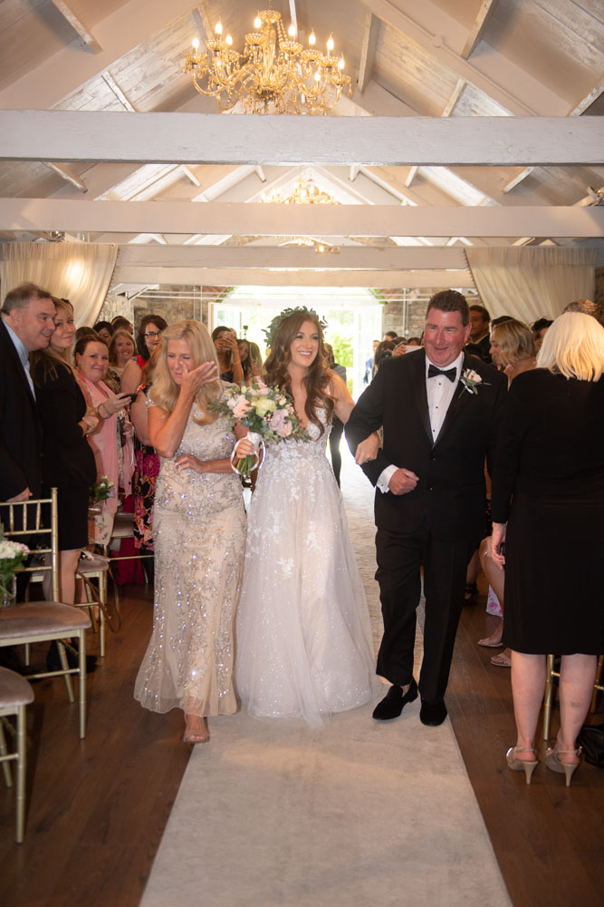Bride walking up the aisle with her parents in Ballymagarvey