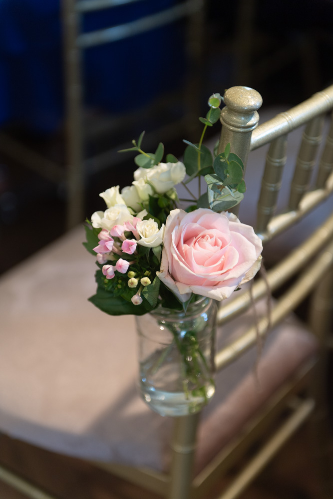 Pink flower in a glass jar hanging on the side of chair for wedding ceremony