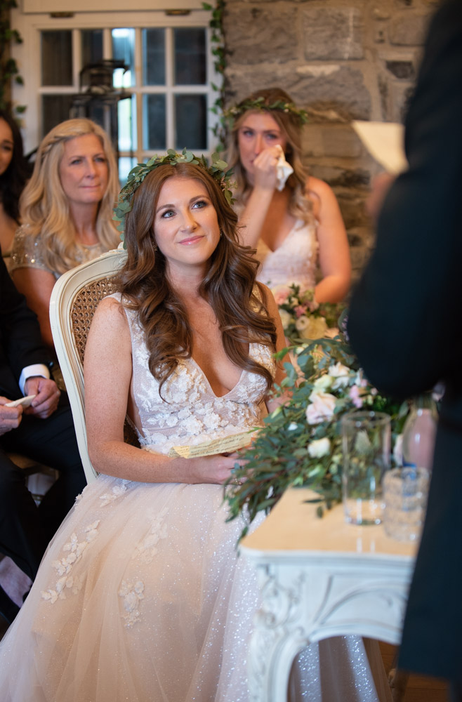 Bride smiling while looking and listening to Groom giving his speech