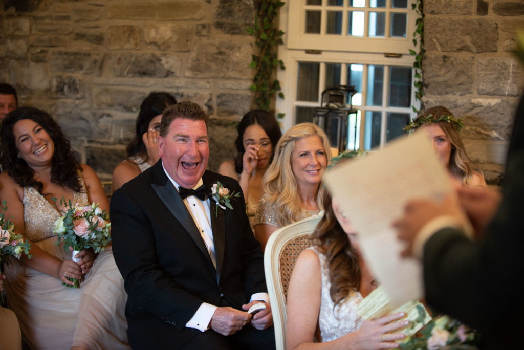 Father of the Bride laughing and looking at the Groom giving his speech