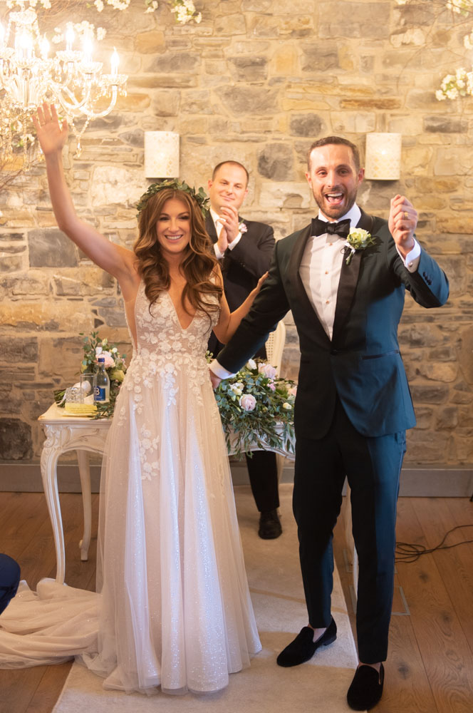 Bride and groom cheering with hands in the air after being announced as just married