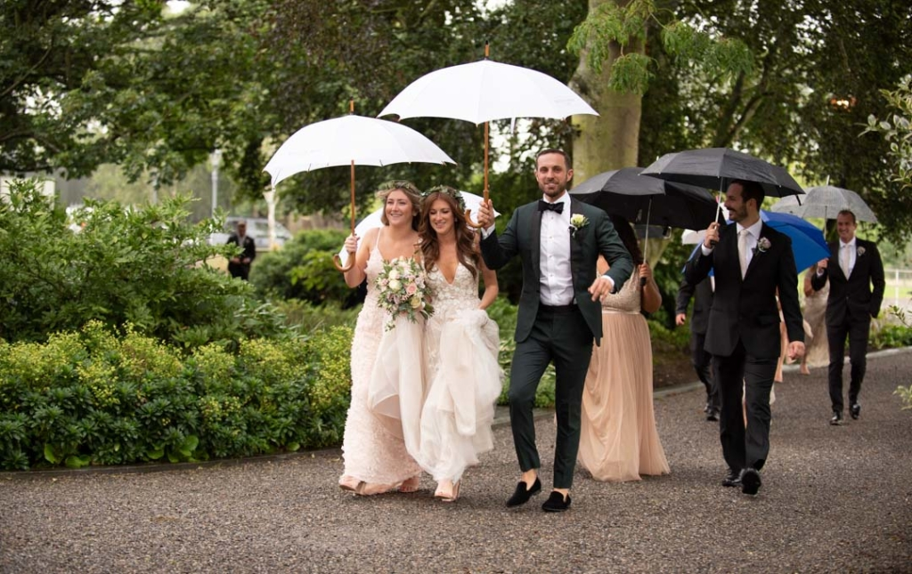 Bridal party walking in the rain with umbrellas at Ballymagarvey village