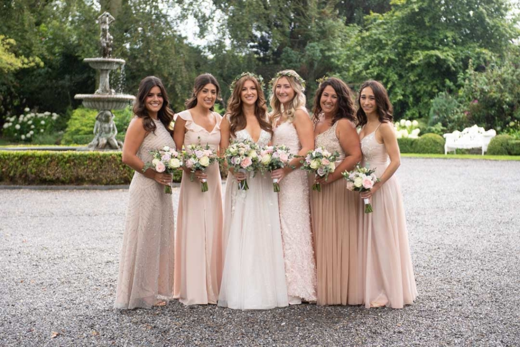 Bride and Bridesmaids in blush dresses holding flowers at Ballymagarvey