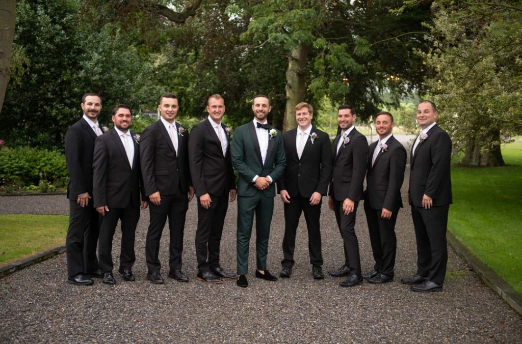 Groom in green suit standing with his groomsmen who are dressed in black suits